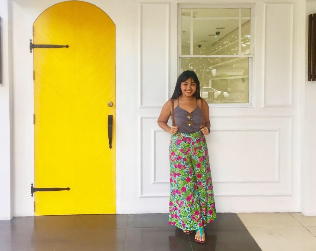 Technopreneur Meryl Jalani posing in front of white wall and yellow door