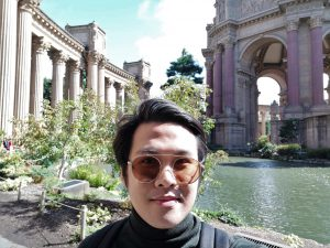Man in shades posing in front of a fountain