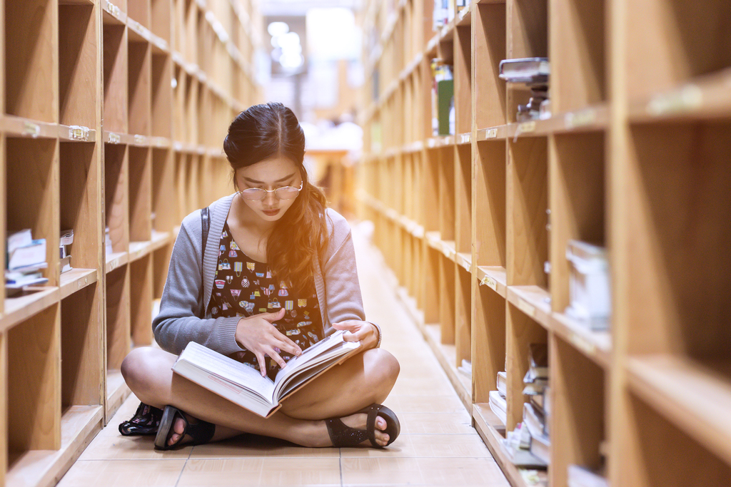 girl reading book while sitting on the floor between bookshelves