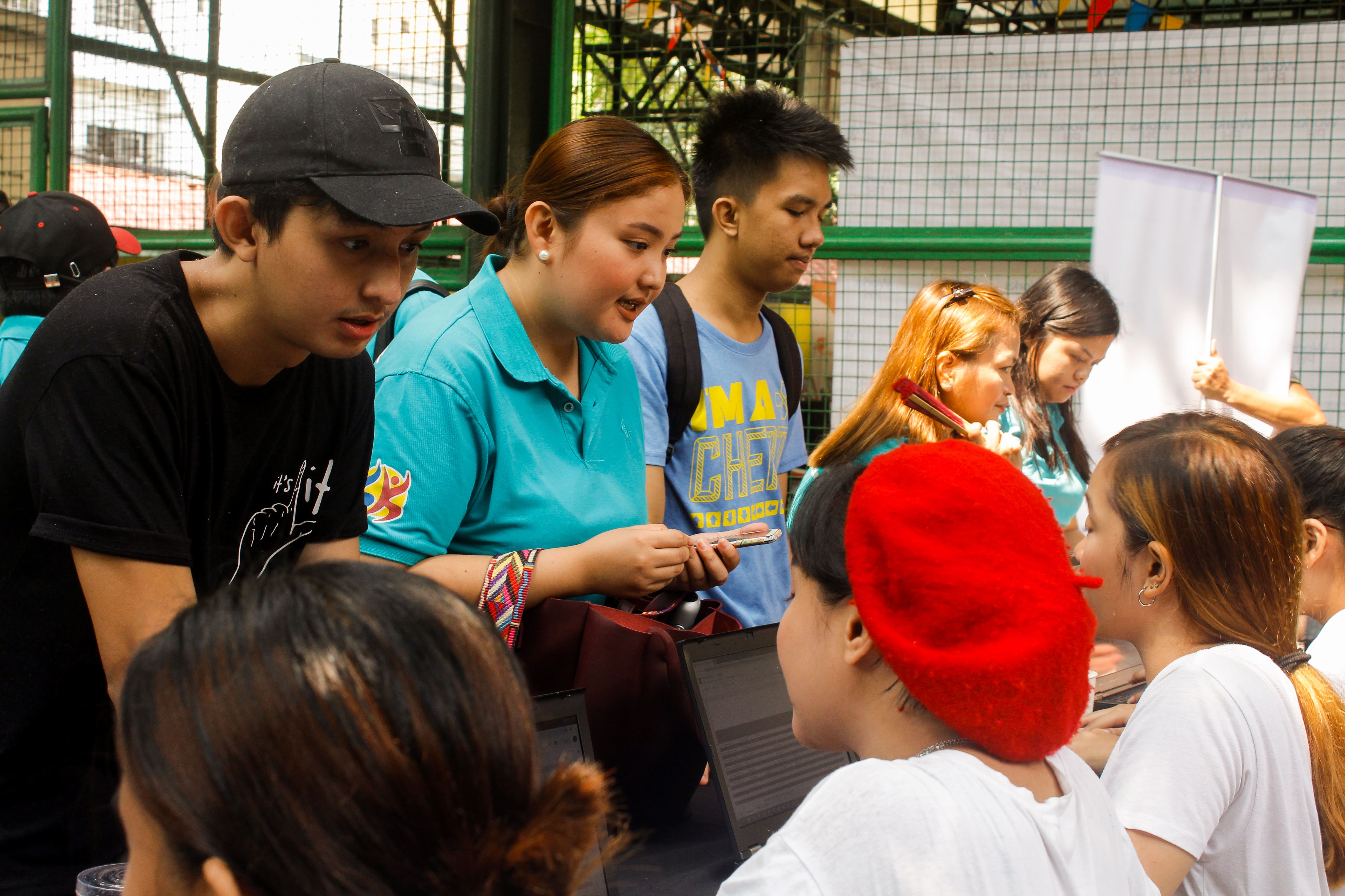 young people inquiring at an information booth