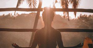 woman meditating under the sun