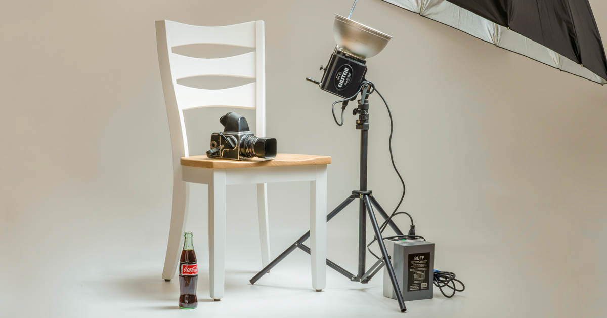 photo studio with camera, lights, chair, and bottle product