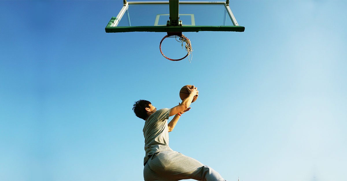 young man dunking a basketball in the ring