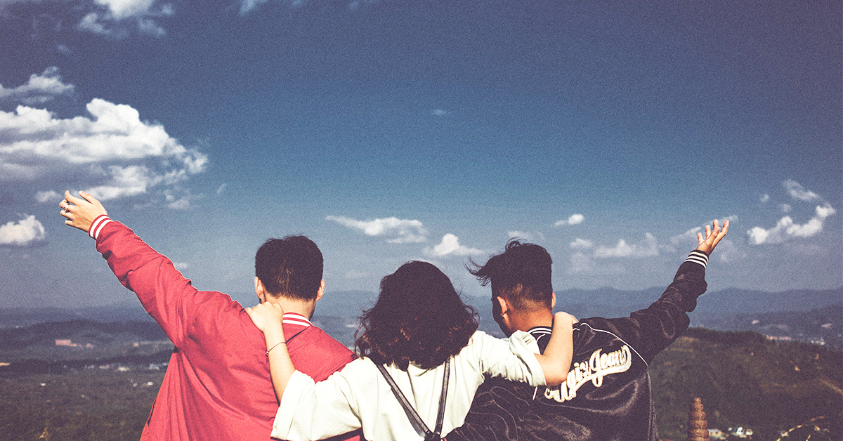 three friends looking out from a mountain view
