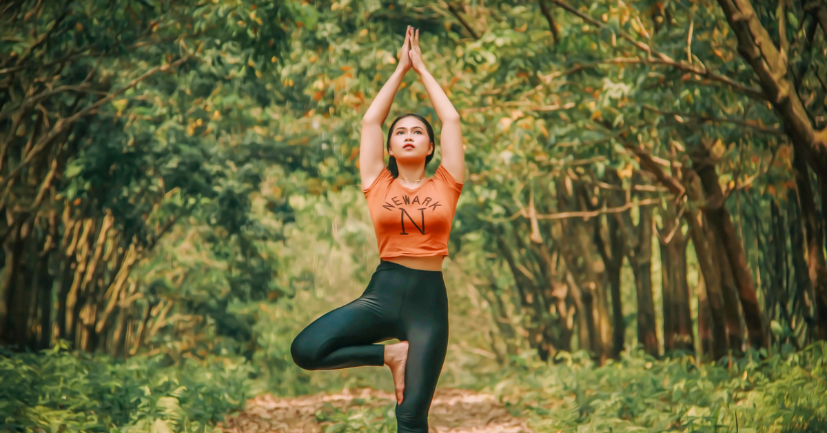 girl doing a yoga pose with arms raised and hands joined together