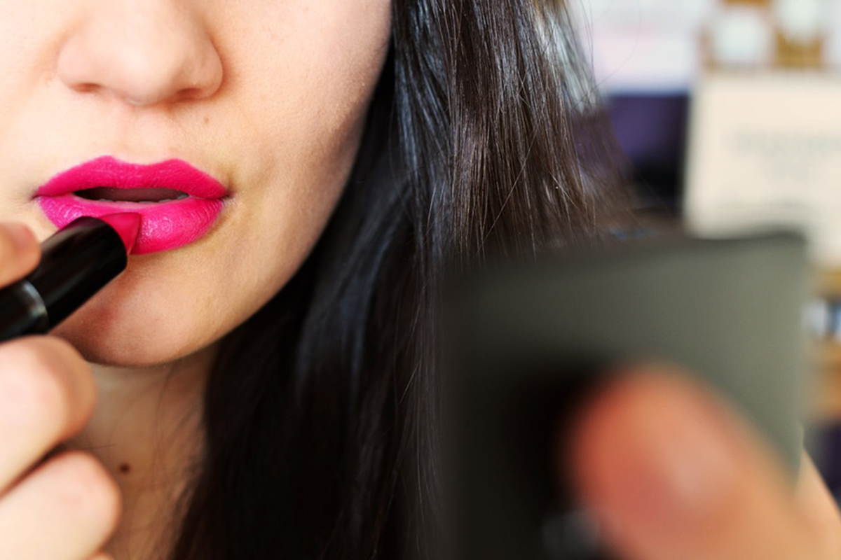 girl applying pink lipstick in front of mirror