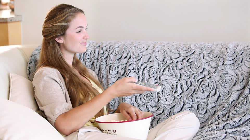woman eating popcorn on sofa