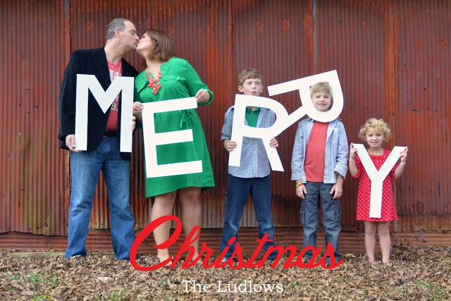 family holding christmas letter cutouts