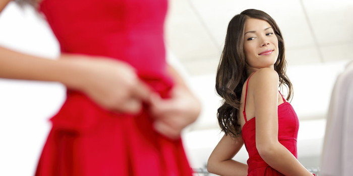 woman wearing red dress looking at mirror