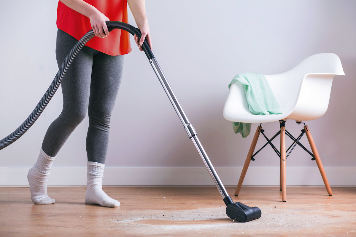 Close-up of woman vacuuming the dust of the floor at the house