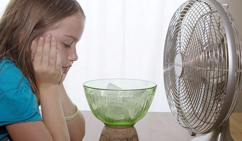 girl stands in front of electric fan and ice bowl