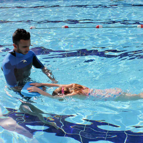 swimming coach guiding student