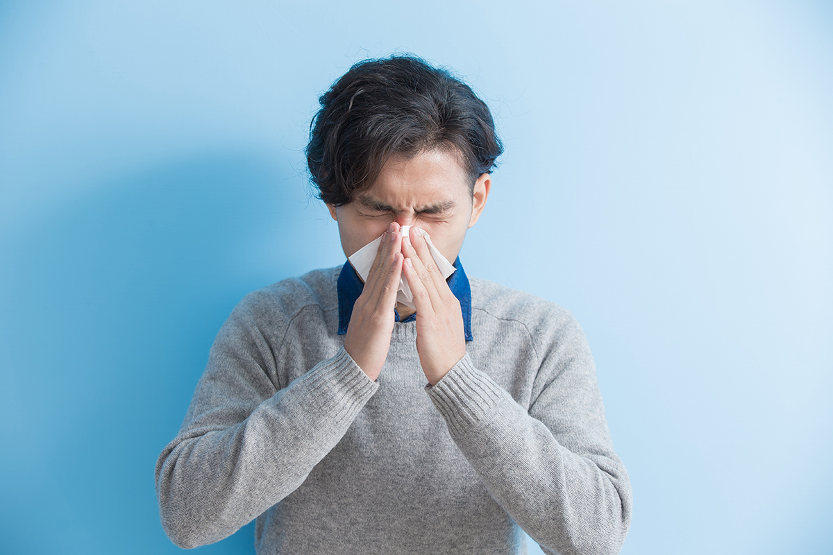 man is sick and sneezing with blue background, asian