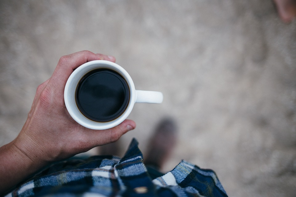 hand holding a cup with coffee