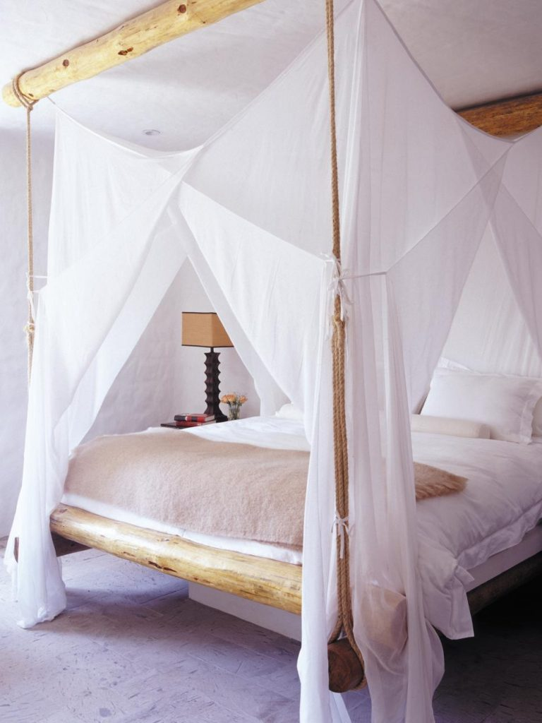 wooden bed with canopy and white sheets