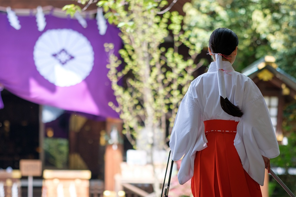 Miko (shrine maiden) in shinto shrine Tokyo perform sacred tasks