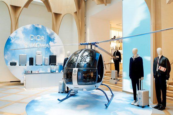 DIOR and RIMOWA別注行李系列率先於十月在香榭麗舍大道專門店的主題場景裝置中亮相,當中包括一架機身有「DIOR RIMOWA」字樣的銀色直昇機點出度假主題。