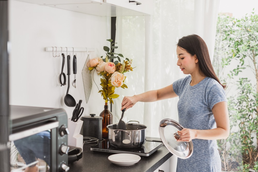 Young Asian woman making healthy food in kitchen at home