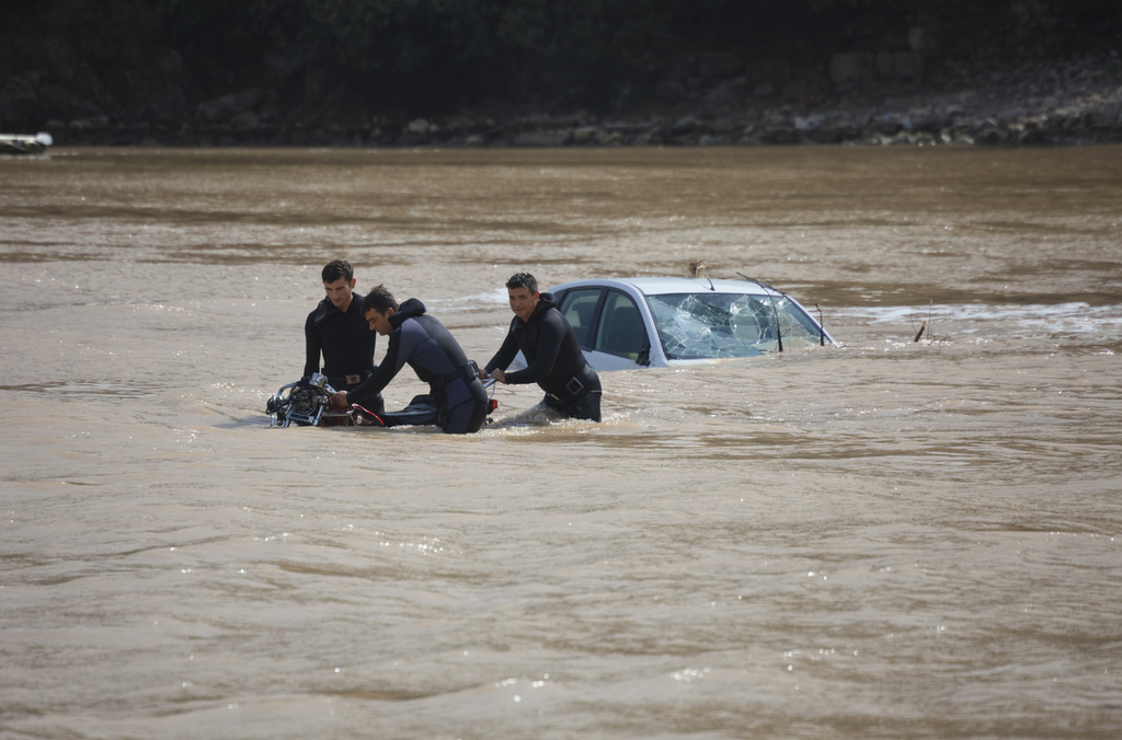Olympos, Turkey - October 14, 2009: Frogmen recovering motorcycle near sunken car in Mediterranean Sea in Olympos, Turkey. Olympos, a famous holiday spot in Antalyas Kumluca district, was hit by floods. The floods swept away about 50 cars from the road into the sea.