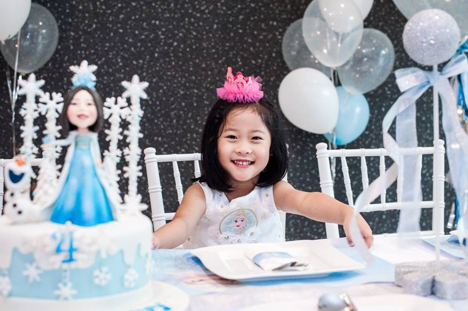 Little Indy with her Frozen, Elsa and Anna birthday party including backdrop, table setting, decoration and balloons