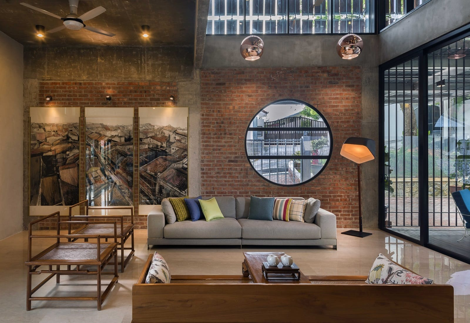 Rustic styled living area features red brick walls and exposed concrete finishes.