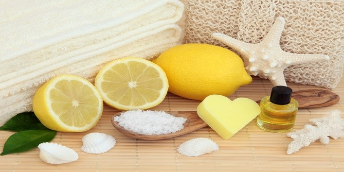 Lemon fruit halves with spa accessories of sea salt, cream towels, exfloiating scrub, aromatherapy essential oil bottle and sea shells over bamboo background.