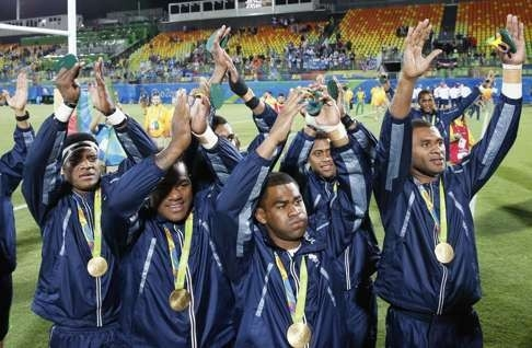 Fiji team members salute the crowd after beating Britain 43-7. Photo: Kyodo