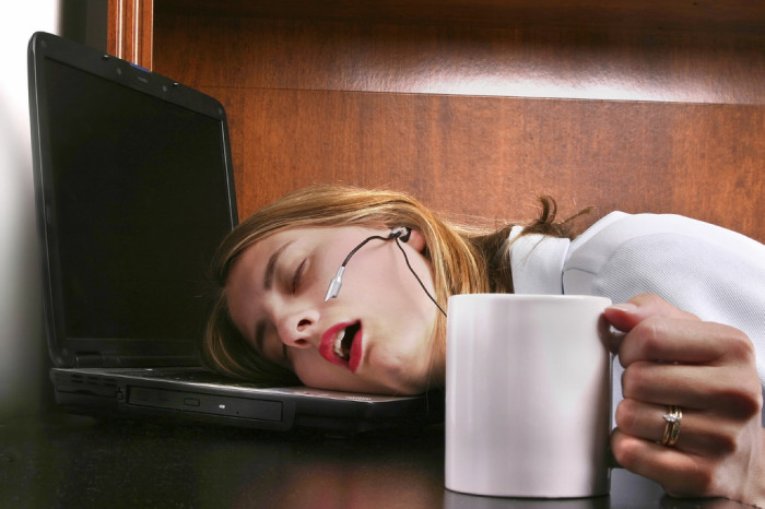 woman tired and asleep on keyboard at work