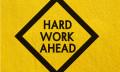 yellow sign warning of hard work ahead
