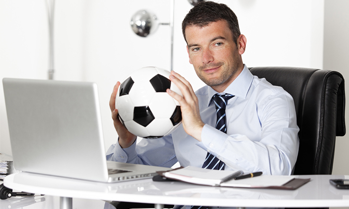 Businessman holding football to show athletes make better employees