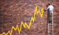 Man spray painting graph on wall
