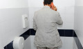 Man taking a call in the toilet to show weirdest places for taking conference calls