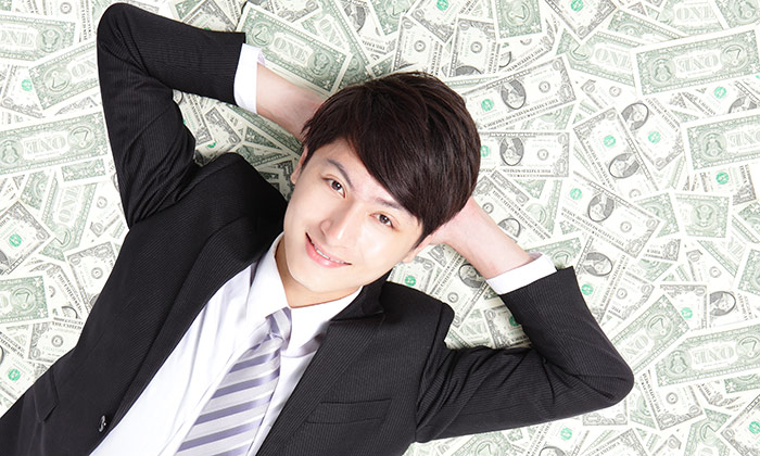 Man lying on top of money to show more Billionaires in Singapore