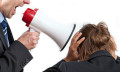 Boss holding loudspeaker over staff to show are you encouraging staff to bully one another?