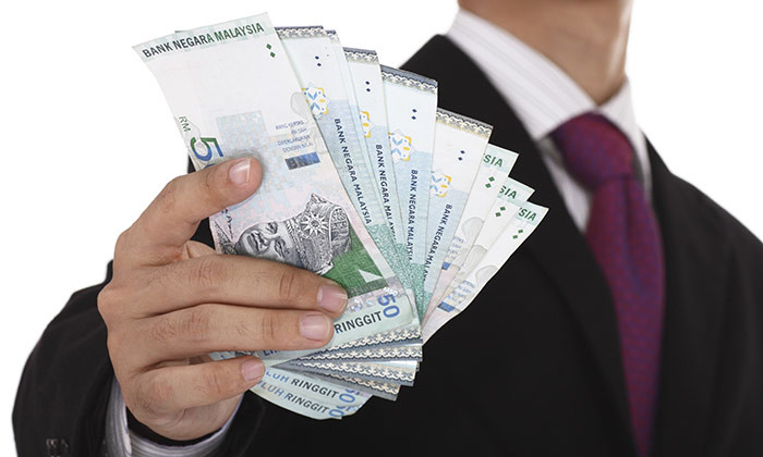 Businessman holding Malaysian money