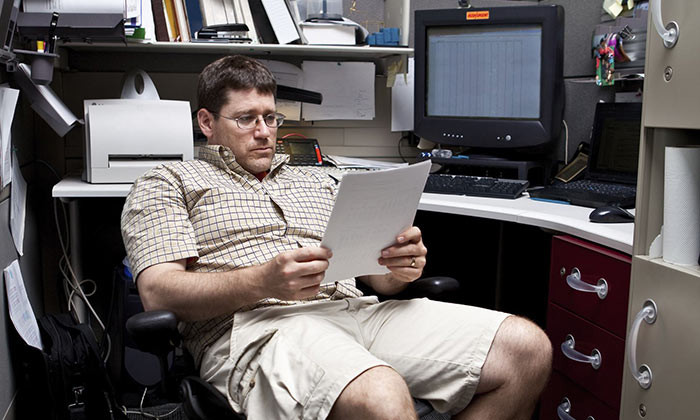 Man in shorts and sandals in the office.