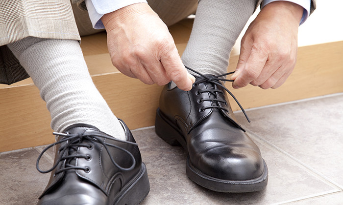 Older employee putting on work shoes, hr