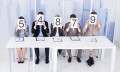 Business people holding up score cards, hr