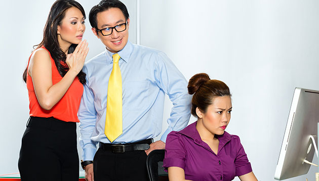 gossiping about colleague in office-123RF