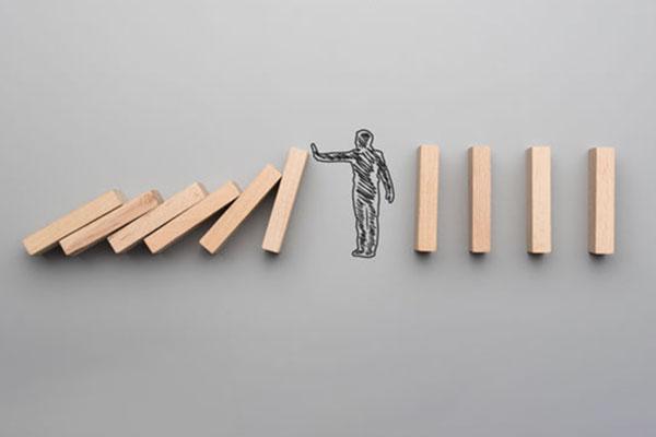 man-stopping-dominos-123RF