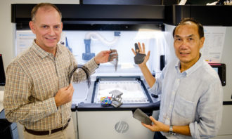 Co-directors of the HP-NTU Corporate Lab, NTU Associate Professor Tan Ming Jen (right) and Mike Reagan (left) holding up 3D-printed products from HP Jet Fusion printers which can include colour as well as print in complex shapes and with different material properties.
