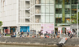 People-sitting-along-Singapore-river-123RF