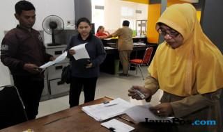 LAYANI WARGA: Seorang aparatur sipil negara (ASN) di kecamatan Tandes Surabaya, melayani pengurusan administrasi warga di kantor kecamatan beberapa wa