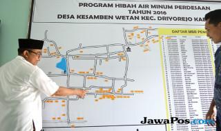 Pengelola Hippam Tirto Bening dengan gambaran alur distribusi air minum Desa Kesamben Wetan, Driyorejo, Gresik.