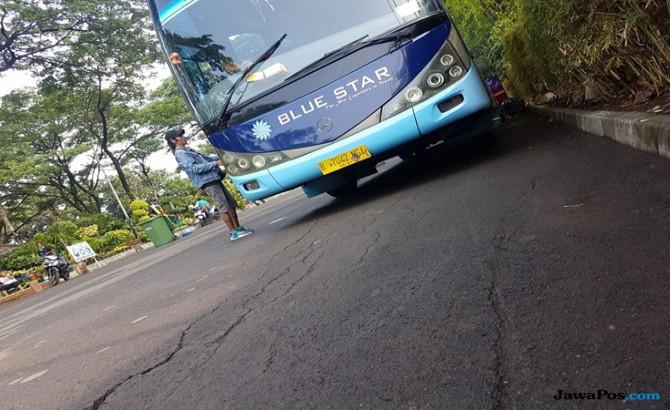 Seorang preman mendekati sopir bus dan meminta uang kepada sopir bus.
