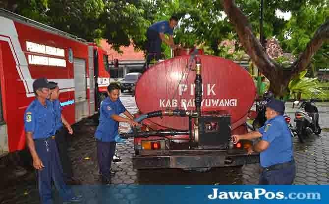 SIAGA: Petugas regu pemadam kebakaran (PMK) Banyuwangi saat memeriksa kondisi mobil tangki penyuplai air