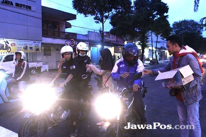 BERBAGAI: Kader DPK GMNI Poliwangi membagikan takjil di jalan Kecamatan Giri.