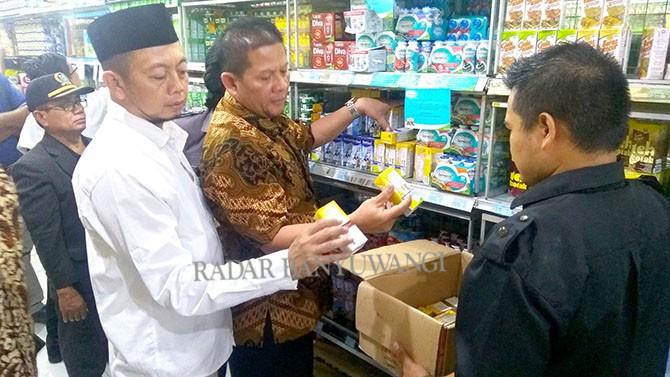 MINTA DITARIK: Handoko dan Andik Purwanto mengambil susu siap minum kemasan kotak yang hampir kedaluwarsa di Vionata kemarin (31/5).