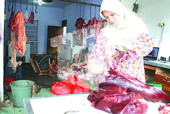 JAGAL: Mantili memotong daging sapi di tokonya Desa Genteng Wetan, Kecamatan Genteng, kemarin (7/6).