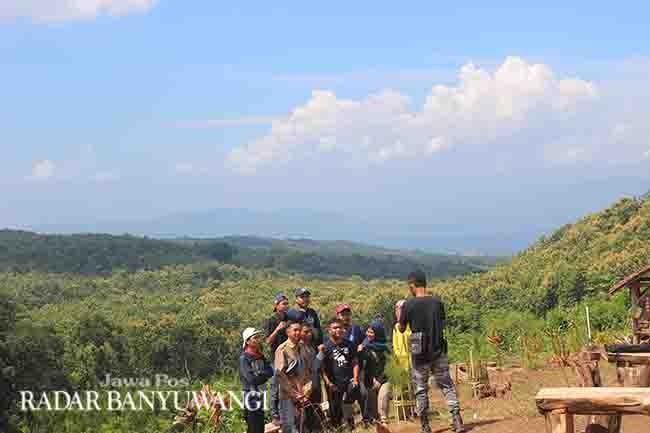 LATAR SELAT BALI: Sejumlah pengunjung berswafoto di Puncak Asmoro di Dusun Kacangan, Kelurahan Gombengsari, Kecamatan Kalipuro.